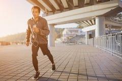 跑在户外、秋天和听的音乐,有吸引力的深色皮肤的赛跑者的年轻人适合的人快速地跑步,体育 免版税库存图片