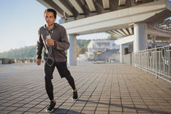跑在户外、秋天和听的音乐,有吸引力的深色皮肤的赛跑者的年轻人适合的人快速地跑步,体育 库存图片