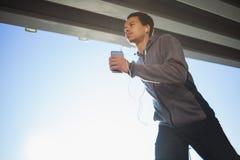跑在户外、秋天和听的音乐,有吸引力的深色皮肤的赛跑者的年轻人适合的人快速地跑步,体育 免版税库存照片