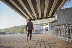 跑在户外,秋天,有吸引力的深色皮肤的赛跑者的年轻人适合的人快速地跑步,体育概念 免版税库存图片