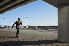 跑在户外,秋天,有吸引力的深色皮肤的赛跑者的年轻人适合的人快速地跑步,体育概念 免版税库存照片