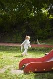 跑在操场附近的美丽的女孩从她的母亲的孩子停放在宜人的太阳下 免版税图库摄影