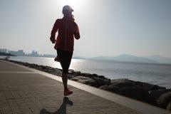 跑在日出海边的健身妇女 免版税库存照片
