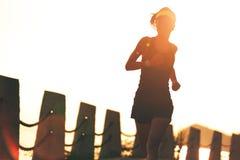 跑在日出海边的年轻健身妇女 图库摄影