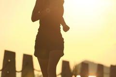 跑在日出海边的年轻健身妇女 免版税库存照片