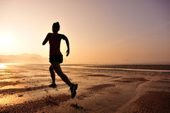 跑在日出海滩的妇女 免版税图库摄影
