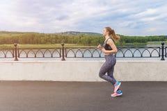 跑在日出的女孩在江边的城市 免版税库存照片