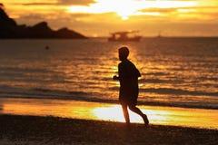 跑在日出的海滩的年轻人剪影 库存图片