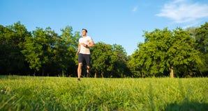 跑在日落期间的一个英俊的年轻人在公园 免版税图库摄影