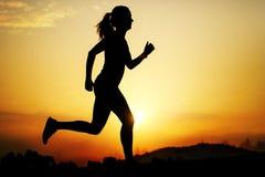 跑在日落的女孩剪影 免版税库存照片