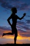 跑在日落的妇女的剪影 库存图片