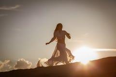跑在日落的美丽的妇女 免版税图库摄影