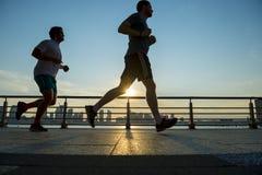跑在日落纽约的慢跑者 免版税库存图片