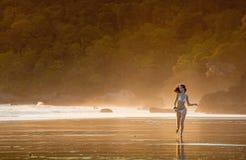 跑在早晨薄雾的一个海滩的年轻美丽的女孩 免版税图库摄影