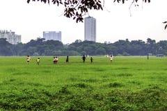 跑在春天公园的孩子在便衣调遣 免版税库存图片
