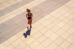 跑在晴天的年轻人适合的妇女在城市 库存图片