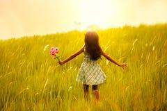 跑在有日落的草甸的小女孩 免版税库存图片