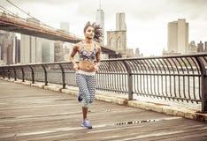 跑在有纽约地平线的码头的女孩 免版税库存照片