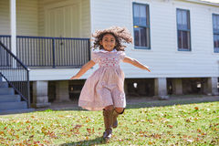 跑在有花的公园的孩子女孩穿戴 免版税库存图片