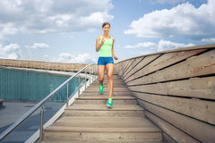 跑在木台阶的女运动员在蓝色多云天空下 免版税图库摄影