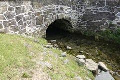 跑在桥梁下的一条小小河 免版税库存照片