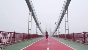 跑在桥梁的年轻胖的白种人女孩 前面射击了慢动作 紫色成套装备 股票录像