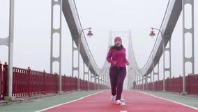 跑在桥梁的年轻胖的白种人女孩 疲乏的中止和舒展 前面射击 紫色成套装备 影视素材