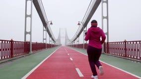 跑在桥梁的年轻胖的白种人女孩 r 紫色成套装备 影视素材