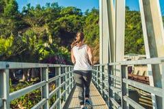 跑在桥梁的美丽的妇女在日落期间 免版税图库摄影
