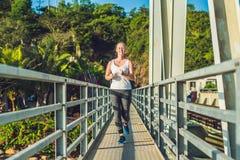 跑在桥梁的美丽的妇女在日落期间 图库摄影