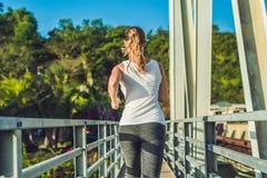 跑在桥梁的美丽的妇女在日落期间 库存照片