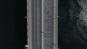 跑在桥梁的马拉松 垂直的移动式摄影车被射击的顶视图慢动作 股票录像