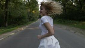 跑在森林公路和微笑的华美的白肤金发的可爱的妇女- 影视素材