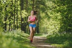 跑在森林足迹和微笑的健身女孩 免版税库存照片