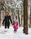 跑在森林里的妈妈和女儿通过雪 免版税库存图片