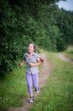 跑在森林里的青少年的女孩 免版税库存照片