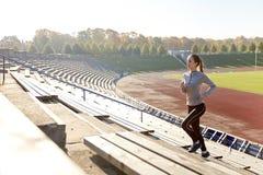 跑在楼上在体育场的愉快的少妇 免版税库存图片