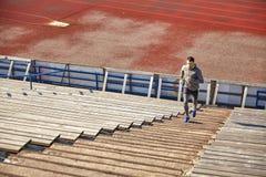 跑在楼上在体育场的愉快的年轻人 免版税库存图片