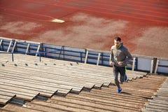 跑在楼上在体育场的愉快的年轻人 库存图片