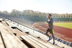 跑在楼上在体育场的愉快的年轻人 图库摄影