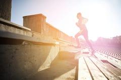 跑在楼上在体育场的愉快的年轻人 免版税库存照片