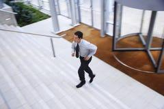 跑在楼上在办公室大厅的商人 免版税库存图片