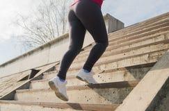 跑在楼上在运动鞋的赛跑者脚特写镜头 免版税库存照片