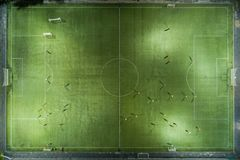 跑在橄榄球场附近的足球运动员 免版税库存照片