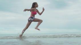 跑在水浪花慢动作股票英尺长度录影的快乐的愉快的女孩 影视素材