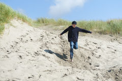 跑在沙丘下的男孩 免版税库存照片