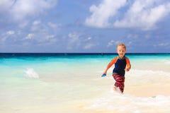 跑在沙子热带海滩的小男孩 免版税库存照片