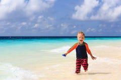 跑在沙子热带海滩的小男孩 免版税库存图片