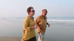 跑在沙滩的活跃资深夫妇在日出 股票录像