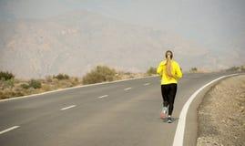 跑在沙漠山柏油路的后面观点的年轻可爱的体育妇女 图库摄影